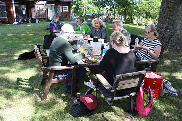 Foto av guiderna som äter medhavd lunch vid Bull-August gård.
