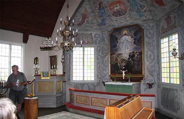 Anders Djerf visar sin morfars, Harald Lindberg, målningar i Arholma kyrka. Foto: Anette Hallsenius.