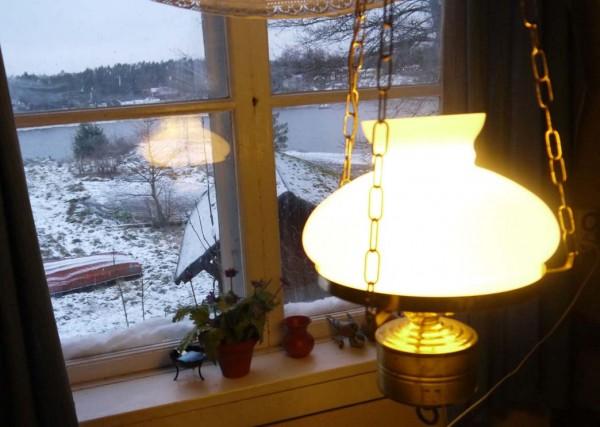 Snöig utsikt genom stugfönster i Rumshamn.