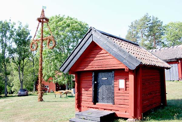 Foto av brännvinsbod och midsommarstång på Kista hembygdsgård.